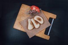 Łeb jarskie fasole z pomidorem Veg kanapka Przekąska na łupku Wznoszący toast chleb Biały chleb z sezamowymi ziarnami na a Zdjęcia Royalty Free