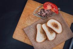 Łeb jarskie fasole z pomidorem Veg kanapka Przekąska na łupku Wznoszący toast chleb Biały chleb z sezamowymi ziarnami na a Zdjęcie Stock