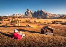 Łgarska kobieta na wzgórzu jest przyglądająca na łąkach i górach obrazy stock