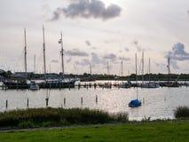 Łodzie cumowali przy jetties w marina w starym miasteczku Makkum, Friesla zdjęcia stock
