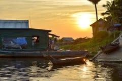 Łodzie i spławowi wioska domy na rzece przy zmierzchem obraz royalty free