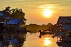 Łodzie i spławowi wioska domy na rzece przy zmierzchem zdjęcia stock