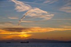 Łodzie na horyzoncie przy zmierzchem pod chmurnym niebem obrazy stock