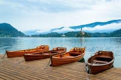 Łodzie na Krwawić jeziorze w Slovenia Halny jezioro z małą wyspą i kościół obraz stock
