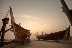 Łodzie na plaży przy wschodu słońca czasem Zdjęcie Stock