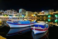 Łodzie rybackie przy Para outra w nocy mieście Crete, Agios Nikolaos w tle nadmorski restauracje, kawiarnie i Zdjęcia Stock