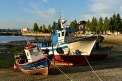 Łodzie rybackie w molu z zmierzchu światłem Mały nabrzeżny wioska port Skały, deptak z drzewami, niebieskie niebo obrazy stock
