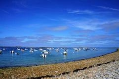 Łodzie unosi się w wodzie blisko otoczaki wyrzucać na brzeg w Brittany zdjęcia stock