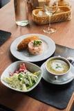 łomotać stół: talerz polewka, risotto z cutlet i warzywo sałatka, obrazy royalty free