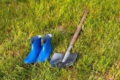 Łopata i gumowi buty Ogrodowi narzędzia na zielonym gazonie Zdjęcie Royalty Free