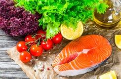 Łososiowi stki, zieleni ziele, czereśniowy pomidor, oliwa z oliwek i cytryna, Zdjęcie Stock
