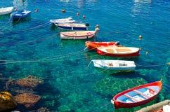 Łowić kolorowe stubarwne łodzie na przejrzystej jasnej wodzie z widocznym dnem w małym kamiennym schronieniu Riomaggiore wioski N fotografia royalty free