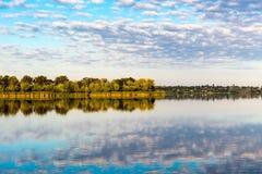 Łowić na brzeg jezioro blisko wioski w wczesnej jesieni Odbicie chmury na wodnej powierzchni rzeka B obraz stock