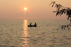 Łowić w łodzi na wieczór jeziorze zdjęcie stock