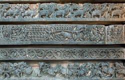 Łowiecka scena i inny drylujemy grafika na tło rzeźbach Mityczni wzory świątynia w Halebidu, India obrazy stock