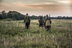 Łowiecka scena z myśliwymi iść przez wiejskiego pola podczas łowieckiego sezonu w chmurzącym dniu podczas zmierzchu z markotnym n Fotografia Stock
