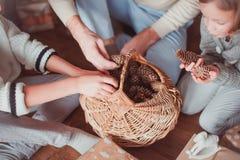 Łozinowego kosza stojaki na drewnianej podłodze Rożki są w koszu Rodzina siedzi na spojrzenie garbkach i podłodze obraz royalty free