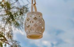 Łozinowy beżowy lampion z białą świeczką wśrodku obwieszenia na szorstkiej brown arkanie zdjęcie stock