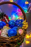 Łozinowy kosz z barwionymi boże narodzenie zabawkami iluminować z festonami zdjęcia stock