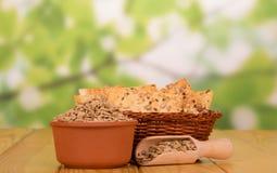 Łozinowy kosz z krakersem, folujący puchar słonecznikowi ziarna, groszkuje w drewnianym sovochke na jasnozielonym, Fotografia Stock