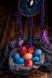 Łozinowy kosz z niezwykłymi barwionymi Wielkanocnymi jajkami i seriami obwieszenie marzy łapacza zdjęcia stock