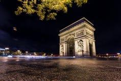 Łuk De Triomphe nocą z światłami ruchu Zdjęcie Royalty Free