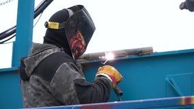 Łuku spaw stal w budowie klamerka Mężczyzna w masce spawa na budowie zbiory wideo