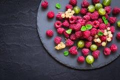Łupkowy naczynie z różnymi jagodami Malinki, agresty, rodzynki na czarnym tle Fotografia Stock