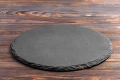Łupkowy talerz na stole Czarny łupku kamień na drewnianym tle kosmos kopii obraz stock