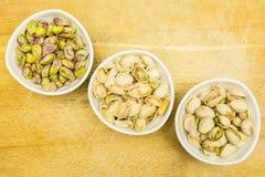 Łuskać pistacjowe dokrętki Całość, nutshell i obrane pistacje w pucharach, na widok obraz royalty free