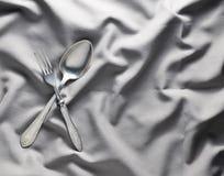 Łyżka i rozwidlenie na szarym jedwabniczym tablecloth Rocznika cutlery kosmos kopii Odgórny widok Zdjęcia Royalty Free