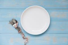 łyżka i rozwidlenie nad biały naczynie z różową Pomiarową taśmą na błękitnym pastelowego koloru drewnianym stole dieting, ciężar  zdjęcia stock