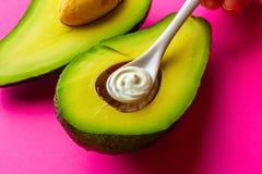 Łyżka kosmetyczna śmietanka w rżniętym avocado na jaskrawym tle Pojęcie skóry opieka, opieka, naturalni kosmetyki fotografia royalty free