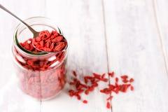 Łyżka pełno zdrowe goji jagody na pełnym słoju Zdjęcia Royalty Free