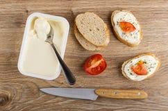 Łyżka w plastikowym słoju z śmietankowym serem, kawałkami chleb, kanapkami z serem, pomidorem i koperem, nóż na stole Odg?rny wid obrazy royalty free