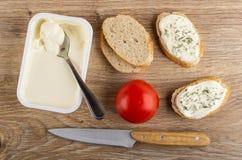 Łyżka w plastikowym słoju z rozciekłym serem, kawałkami chleb, pomidorem, kanapkami z serem i koperem, nóż na stole Odg?rny widok zdjęcie royalty free