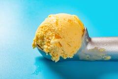 Łyżka z mangową smaku lody piłką na błękitnym tle obraz royalty free