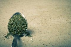 Łyżka z wysuszonym ziele i solą na kamiennym tle stonowany Obraz Royalty Free