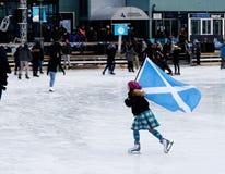 Łyżwiarka niesie Saltire na plenerowym lodowisku w Montreal obraz royalty free