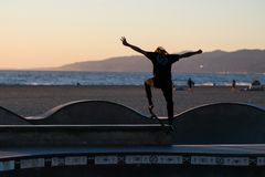 Łyżwiarka w akci przed morzem przy Wenecja ` s skatepark obraz royalty free