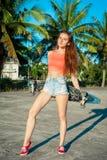 Łyżwiarki dziewczyna pozuje z deskorolka blisko palm na plaży Kobieta w colourful clothers obraz royalty free