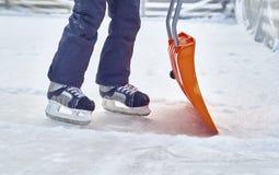 Łyżwiarska chłopiec czyści lodowisko fotografia royalty free