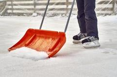 Łyżwiarska chłopiec czyści lodowisko zdjęcie royalty free