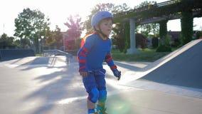 Łyżwowy park, dziecko w bohatera kostium rollerblading na boisku na na wolnym powietrzu zbiory