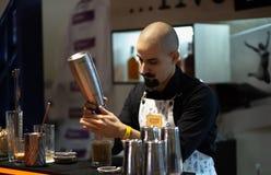 Łysy barman z kręconym wąsy przygotowywa koktajl obraz royalty free