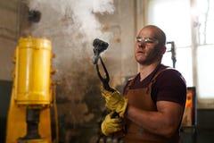 Łysy blacksmith sprawdza metalu kawałek po gaszącego zdjęcie stock