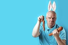 Łysy brutalny mężczyzna w lekkich koszulki i królika ucho W jego rękach trzyma marchewki różny rozmiar zdjęcia royalty free