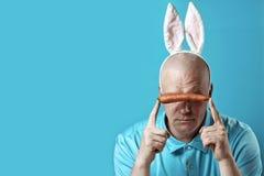 Łysy brutalny mężczyzna w lekkiej koszula i królików ucho W rękach trzyma marchewki która zamyka oczy, obrazy royalty free