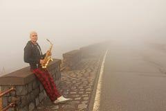 Łysy mężczyzna bawić się na złocistym altowym saksofonie na poboczu, znowu fotografia royalty free