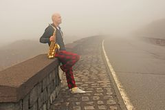 Łysy mężczyzna bawić się na złocistym altowym saksofonie na poboczu, znowu zdjęcia stock